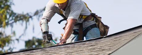 Roofer on a roof nailing shingles